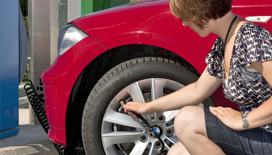Woman checking tire pressure